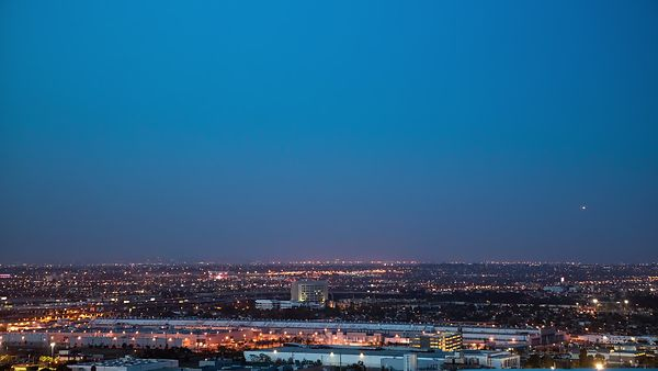 Bird's Eye: Transitioning Blue Hour Over Airplane Landing Flightpath