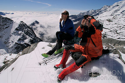 Alpinists scouting a route with binoculars