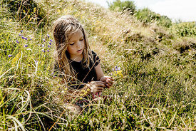 Little girl in the grass picking flowers 4