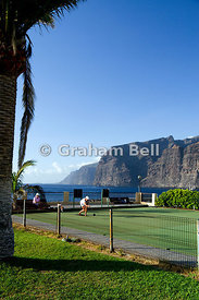 Bowls Player, with the cliffs of Los Gigantes in the distance, Los Gigantes, Tenerife, Canary Islands, Spain.