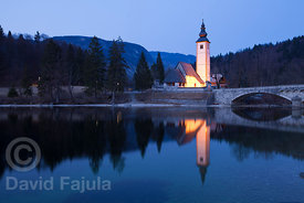 Lake Bohinj (Bohinjsko jezero) at dusk with the  Church dedicated to Saint John the Baptist (Cerkev sv. Janeza Krstnika)