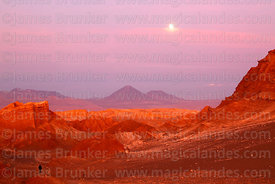 Full moon above rock formations in Valle de la Luna, Licancabur (L) and Juriques (R) volcanos in background, Los Flamencos National Reserve, Chile