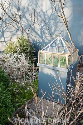 A cast iron Victorian lantern cloche set on a pedestal in a formal kitchen garden surrounded by fruit bushes casting shadows onto the grey wall behind.