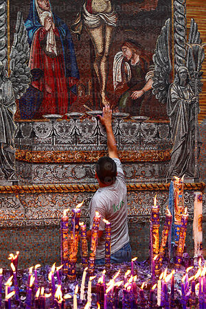 Man blessing offering at feet of Señor de los Milagros mosaic in courtyard behind Las Nazarenas church, Lima, Peru
