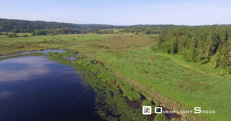 Slow aerial slider action of crystal clear blue lake and green pastures. Clinton Washington State