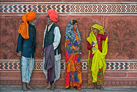 These rural Rajasthani men and women take a break from their visit to Taj Mahal and chat. This photograph was shot against a beautifully carved red sand stone wall, in Fatehpur Sikri complex, Agra