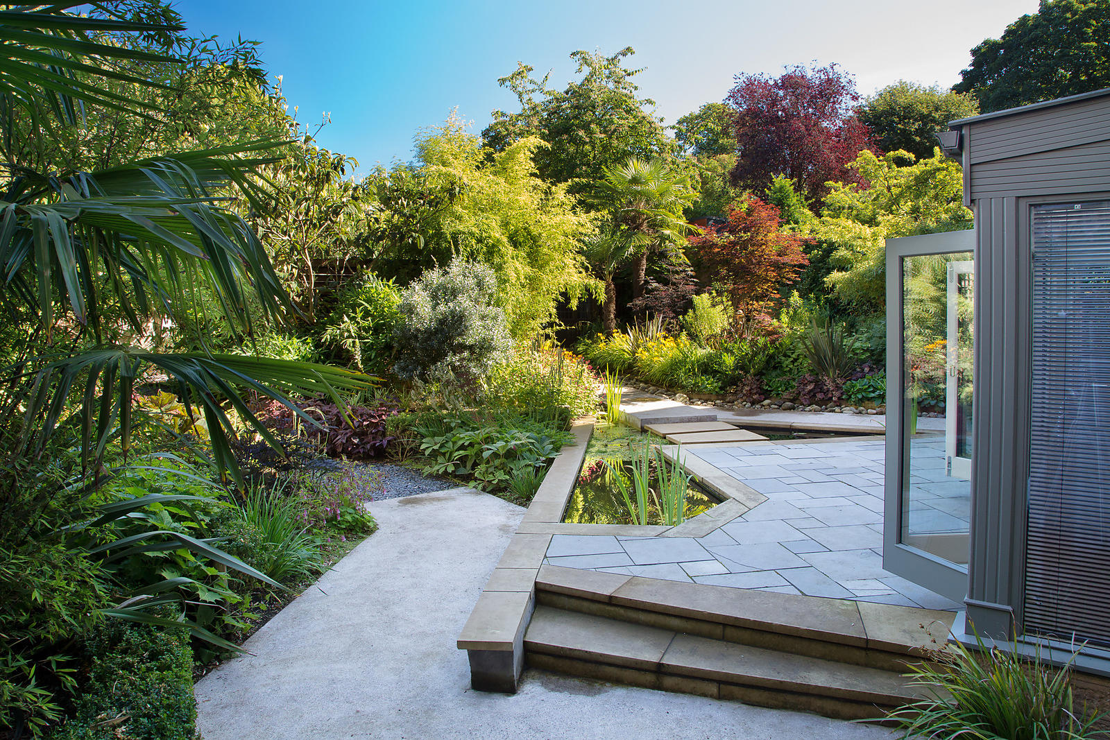 Urban garden featuring contemporary landscaping and planting inspired by south-east Asian jungle