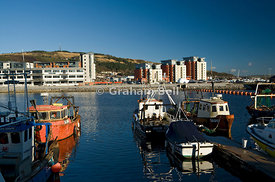 fishing boats moored on river tawe with the SA1 development in the distance swansea south wales uk