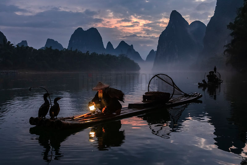 Traditional Fisherman Preparing his Lamp on the Li River.