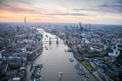 A dusk aerial view looking up the River Thames showing St Katherines Dock on the right of the image, Tower Bridge, The City of London and the Shard.