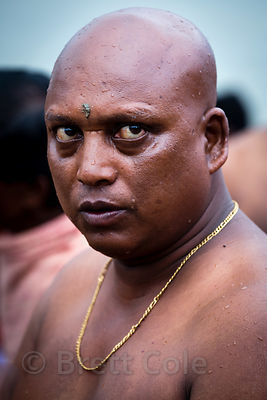 Hindu man with his head shaved to honor deceased relatives during Mahalaya, Babughat, Kolkata, India