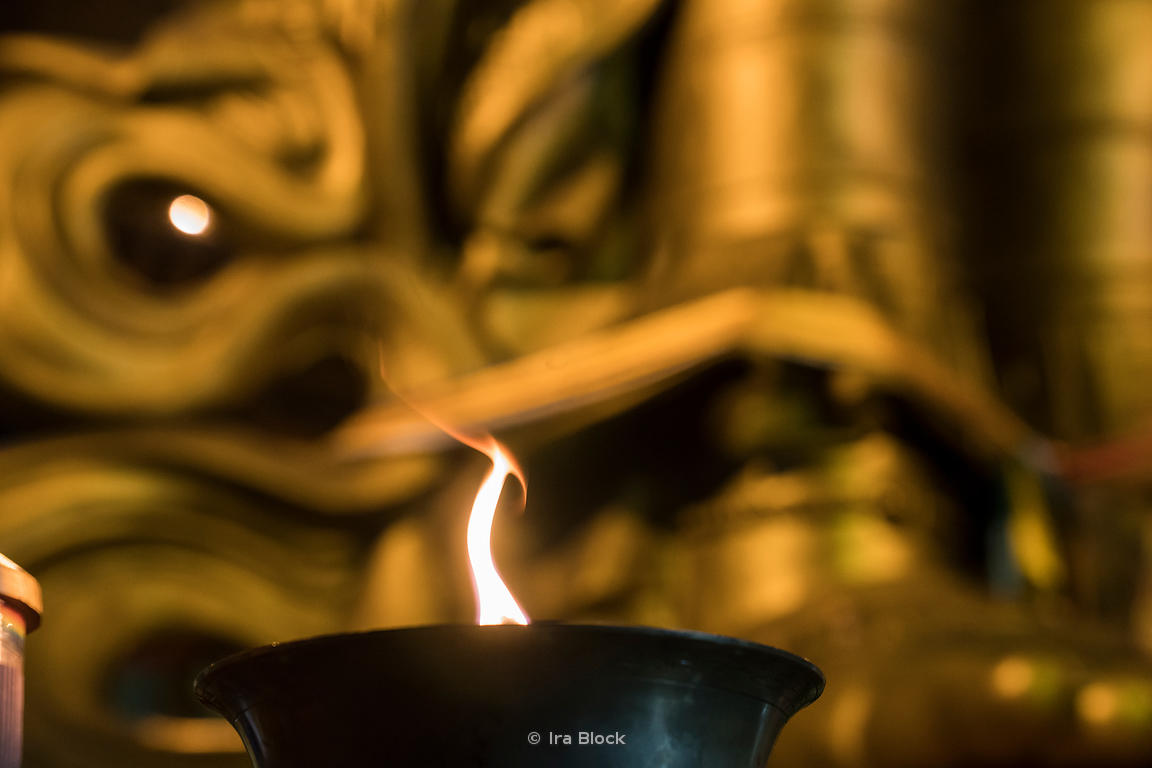 "A flame burns near the statue of Migjid Janraisig at Gandantegchinlen Monastery, a Tibetan-style monastery in Ulaan Baatar, Mongolian.  The Tibetan name translates to the ""Great Place of Complete Joy""."