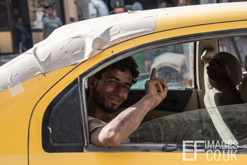 "Moslawi man giving the ""One God"" gesture from the back of a taxi in a recently liberated area of West Mosul. 5th June 2017"