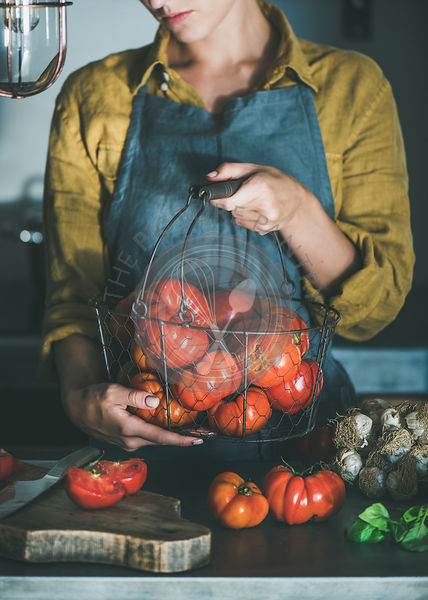 Woman in apron holding basket with heirloom tomatoes