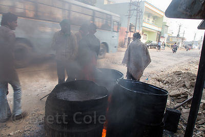 Drums of oil burning and giving off thick black smoke, Rawat Nagar, Ajmer, Rajasthan, India. Air pollution is a major health crisis in India.