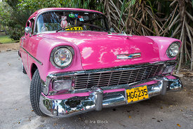 A old pink car used as taxi in Cuba.