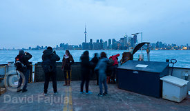 Tourist taking pictures from the ferry, with the Toronto skyline on the background