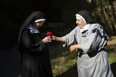 Mother Escolastica presents Mother Noelle with a rose
