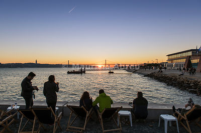 Cafe at the Ribeira das Naus esplanade facing the Tagus river, at sunset. Lisbon, Portugal