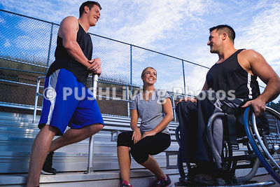 Active guy in a wheelchair talking with friends after a workout