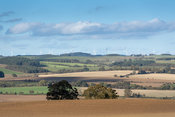 Arable farmland near Hexham, Northumberland, with wind turbines on the horizion. UK.