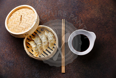 Steamed dumplings Gyoza in bamboo steamer with chopsticks and sauce on brown background