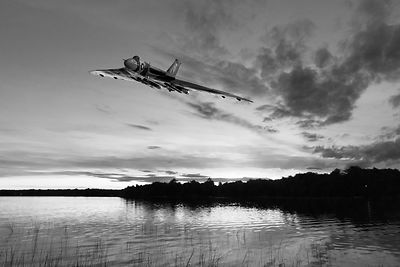 Vulcan low over a sunset lake BW
