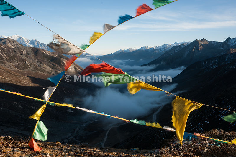 Prayer flags, placed by pilgrims to ensure safe travel, wave over Zheduo Pass, high above the mist-filled valley.
