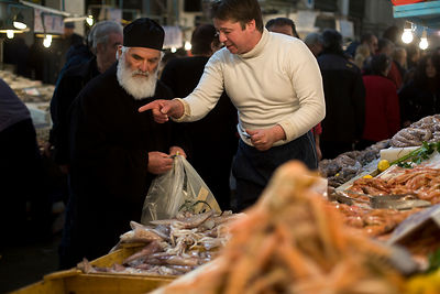 Greece - Athens - A Greek Orthodox priest  buys seafood from a stall in the Athens Central Market