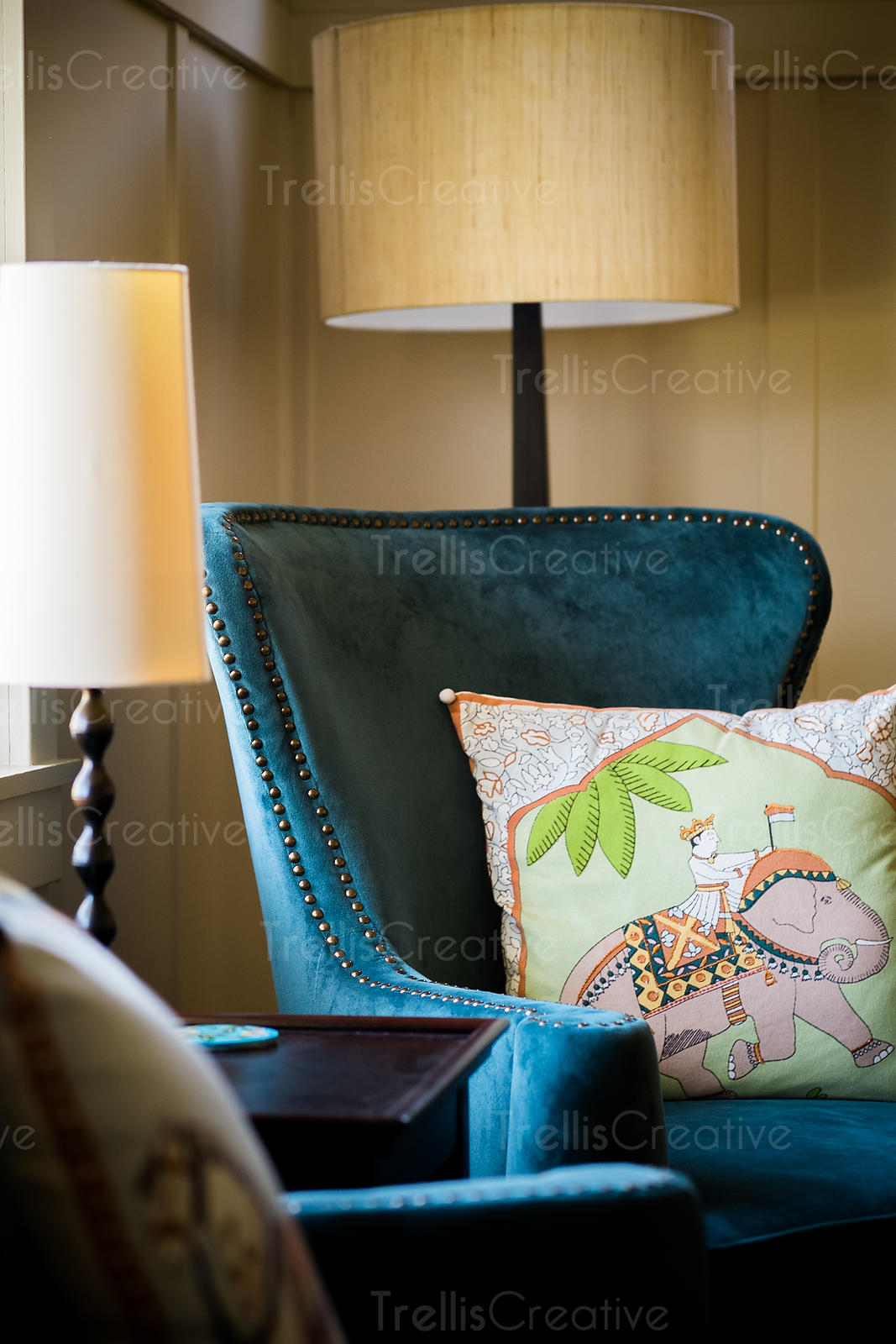 textured decor of a cushion on a blue wingback chair with lamps