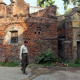 A man walks past a ruined French Colonial building with his lunch pail