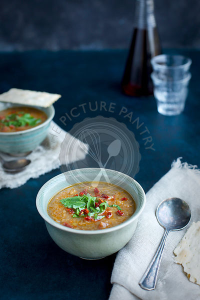 Red Lentil Soup topped with sun dried tomato and arugula in ceramic bowls.