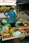 Woman at her market stall selling fruit and vegetables in Pinerolo.
