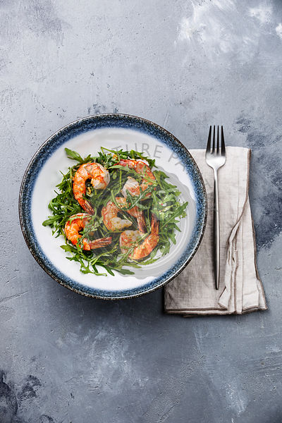 Rocket salad with prawn shrimp on gray concrete background