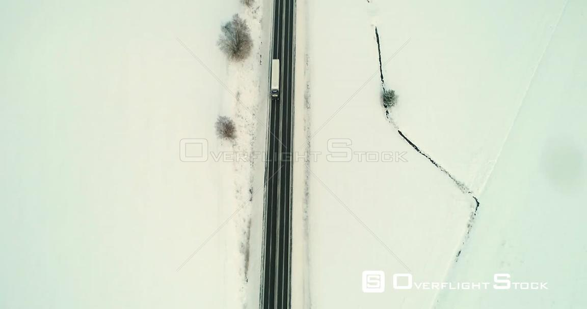 Truck on a Winter Road, Aerial, Tilt Up, Drone Shot, of a Lorry Driving in the Scandinavian Countryside, on a Icy Road, on a Cloudy, Evening, in Uusimaa, Finland