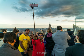 Tourists take photographs on top of the rock in Rockefeller Center, New York City.