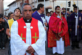 Priest carrying cross during Good Friday procession , Cusco , Peru