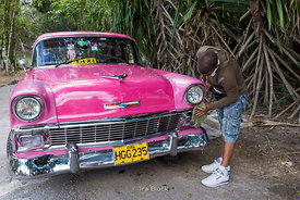 A taxi driver cleaning his old pink car in Cuba.