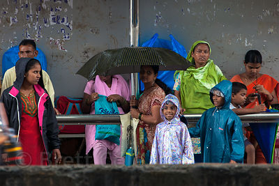 Women and children wait for a bus in monsoon rains in Dharavi, Mumbai, India.