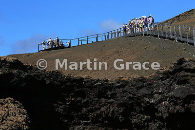 Two tourist groups on the boarded walk to the viewpoint summit of Bartolome Island, Galapagos Islands