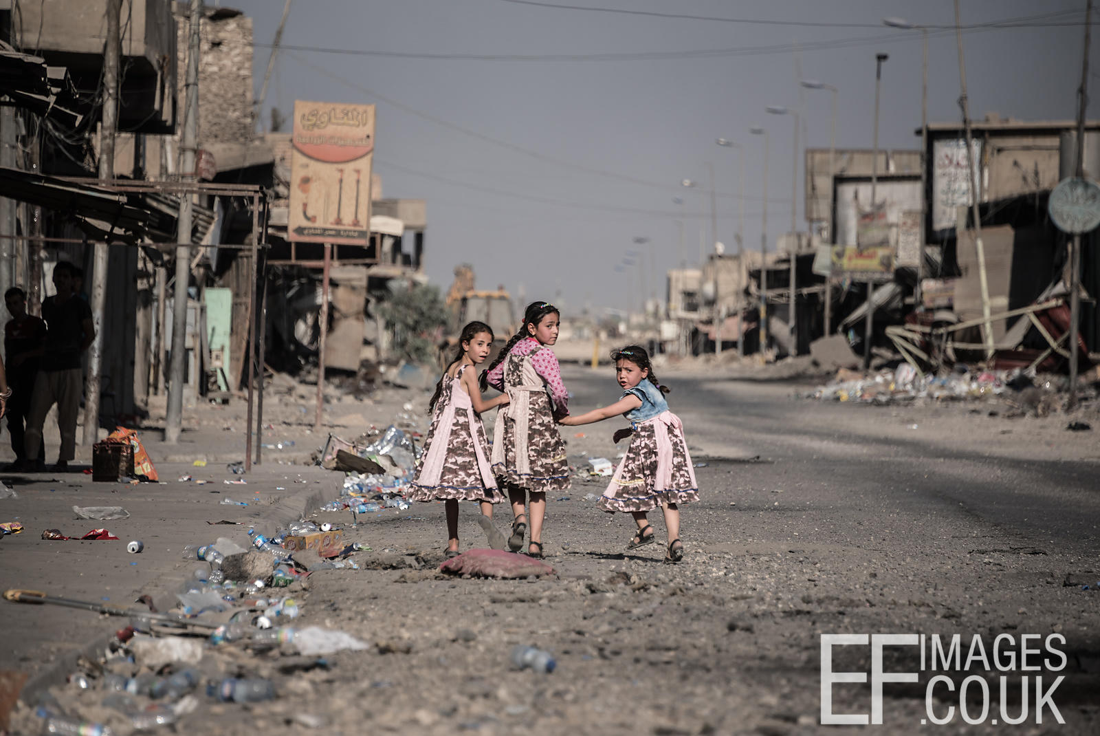 Girls in dresses made from old Soldiers uniforms and pink offcuts walk home in a recently liberated area of West Mosul. July 2017