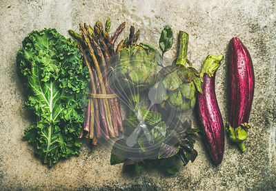 Flat-lay of fresh green and purple vegetables, top view