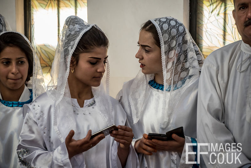 Chaldean Choir Girls Checking Their Mobile Phones During A Maundy Thursday Service By Mar Louis Raphael Sako, Patriarch Of The Chaldean Catholic Church, In Iraq.