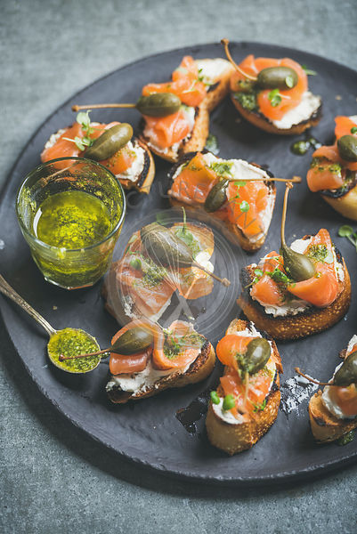 Homemade salmon crostini with cream-cheese, watercress, capers and pesto suace in round black slate stone plate over grey background