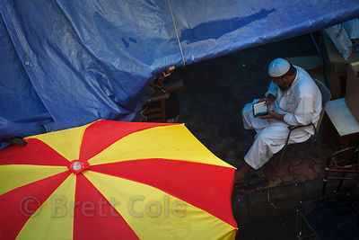A man reads the Koran during a monsoon rain in Bandra East, Mumbai, India.
