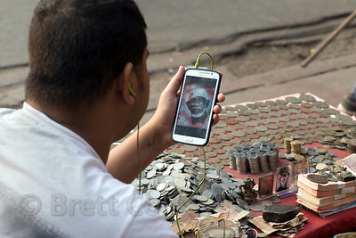 A man selling old coins (fake old coins) looks at an image of Sai Baba on his smartphone, Delhi, India