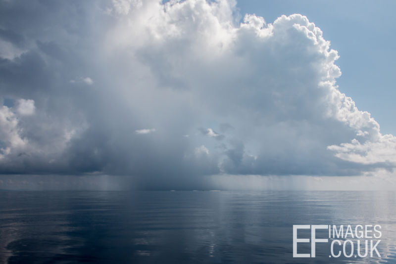 Rain In The Distance Over The Sea With Big Cumulonimbus Clouds, Malaysia