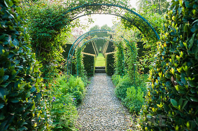 A pebble path leads beneath rose and clematis arches along the garden's central axis between clipped bay,  yew pyramids and fastigiate hornbeams towards the focal point of a stone obelisk. The Old Rectory, Netherbury, Dorset, UK