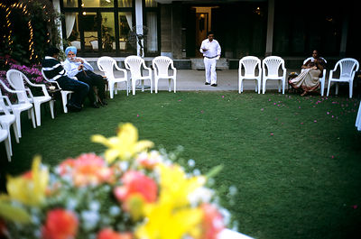 India - Delhi - Men talk at a society garden party
