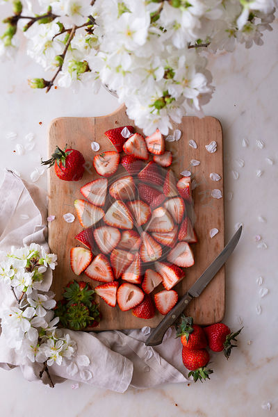 Fresh Strawberries, sliced on a chopping board, surrounded by blossom